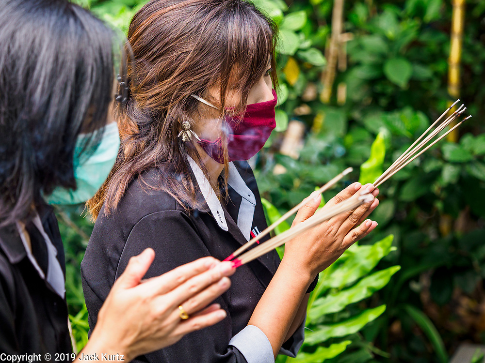 """31 JANUARY 2019 - BANGKOK, THAILAND:   Women wearing breathing masks prays with incense before going to work at an office tower in Bangkok. In an effort to control particulate pollution, the Thai government has asked people not to burn incense or """"gold paper"""" for religious rituals. The Thai government has closed more than 400 schools for the rest of the week because of high levels of pollution in Bangkok. At one point Wednesday, Bangkok had the third highest level of air pollution in the world, only Delhi, India and Lahore, Pakistan were worst. The Thai government has suspended some government construction projects and ordered other projects to take dust abatement measures. Bangkok authorities have also sprayed water into the air in especially polluted intersections to control dust. Bangkok's AQI (Air Quality Index) Thursday morning was 180, which is considered unhealthy for all people.       PHOTO BY JACK KURTZ"""