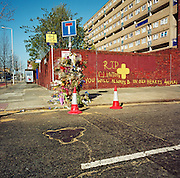 """This memorial has been placed where a young man called 'Clinton' died on the A1206 Manchester Road, London, England, UK. If we drove past this place where someone's life ended, the victim would just be an anonymous statistic but flowers are left to die too and touching poems and dedications are written by family and loved-ones. One reads: """"Your body is soft, not like street, Clinton."""" From a project about makeshift shrines: Britons have long installed memorials in the landscape: Statues and monuments to war heroes, Princesses and the socially privileged. But nowadays we lay wreaths to those who die suddenly - ordinary folk killed as pedestrians, as drivers or by alcohol, all celebrated on our roadsides and in cities with simple, haunting roadside remembrances."""