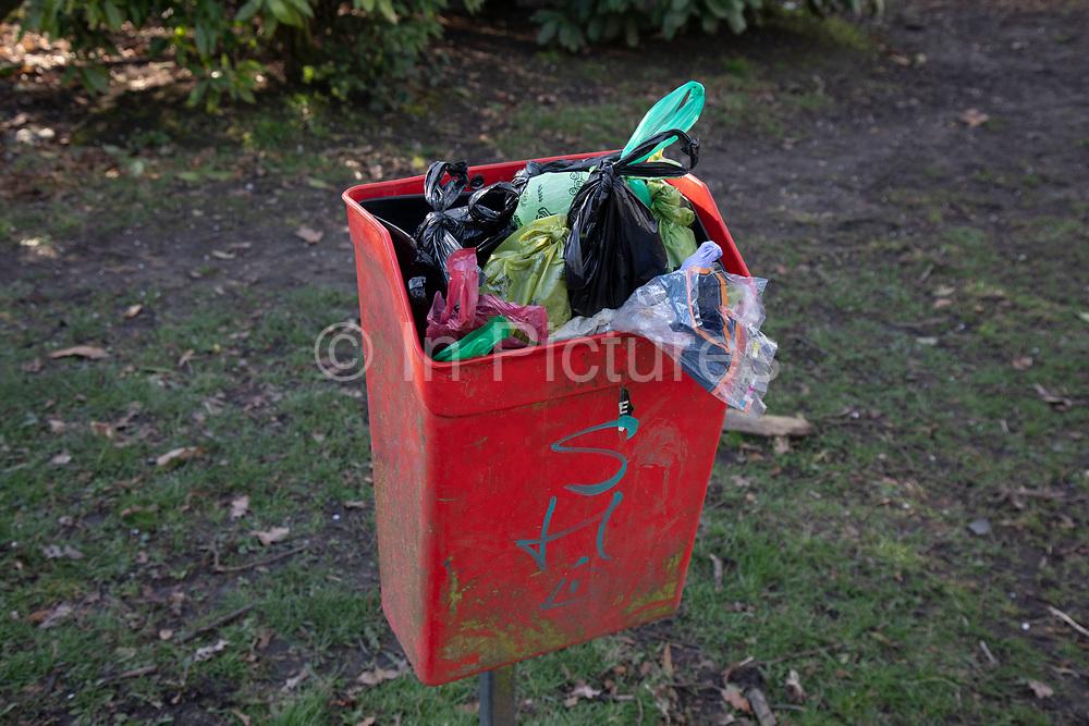 Dog bin overflows full of bags of dog poo bags in Birmingham, United Kingdom.