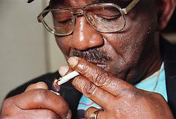 Portrait of man lighting cigarette,