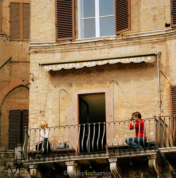 Tourists pose for photos on a cafe balcony above the Piazza Del Campo, Siena, Tuscany, Italy