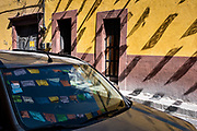 Paper fiesta banners are reflected on a car windshield along Quebrada Street in the historic center of San Miguel de Allende, Guanajuato, Mexico.
