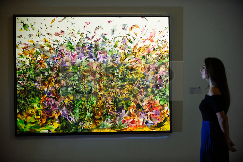 "© Licensed to London News Pictures. 18/10/2019. LONDON, UK. A staff member poses with ""Stardust"", 2011, by Ali Banisadr (Est. GBP280,000-350,000).  Preview of Islamic, Indian and Middle Eastern art to be auctioned at Sotheby's, New Bond Street, on 22 and 23 October.  Photo credit: Stephen Chung/LNP"