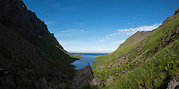 Female hiker overlooks lake in Hermannsdalen valley, Moskenesøy, Lofoten Islands, Norway