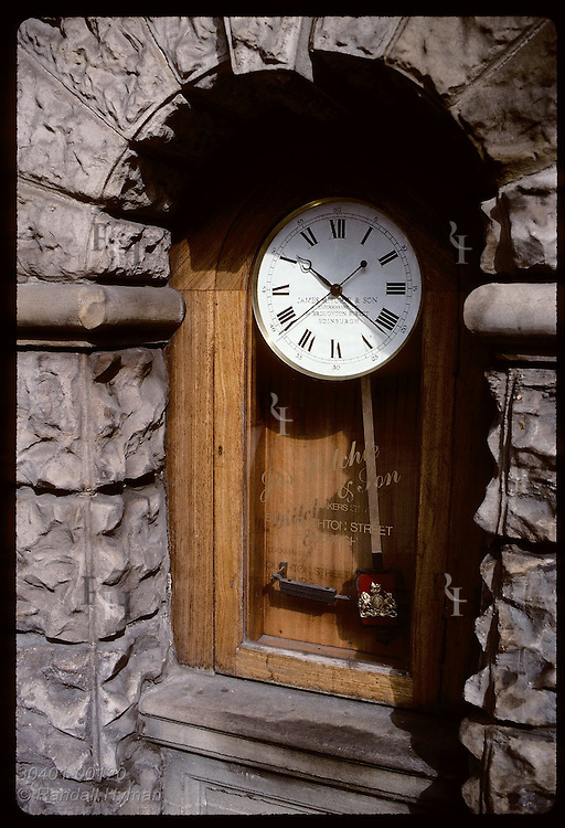 Old clock set into stone wall on downtown street advertises clockmakers' shop in Edinburgh. Scotland