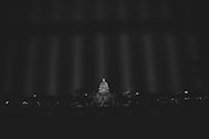 Nighttime view through slits in a recently constructed fence surrounding the Capitol Building in Washington DC on January 21, 2021.