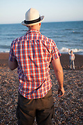 Man on Brighton beach plays with a youngster.