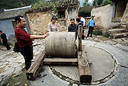 Tourists look at an old fashioned stone mill in the village of Chuandixia. Settlers from Shanxi Province founded the city over 500 years ago, mostly for the business opportunities that abounded on the ancient road from Shanxi Province to Beijing. Wayfarers needed places to stay and food to eat on their rigorous trek through the mountains. The town also served as a postal station. Under these conditions, Chuandixia flourished, even in its position near one of the most remote outposts of the Great Wall.