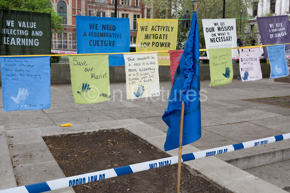 On the 10th consecutive day of protests around London by the climate change campaign Extinction Rebellion, protest flags are draped between statues of historical statesmen, on 24th April 2019, in Parliament Square, Westminster, London England.