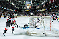 KELOWNA, CANADA - OCTOBER 23: Colby McAuley #14 of Prince George Cougars shoots the puck behind the net of Michael Herringer #30 of Kelowna Rockets on October 23, 2015 at Prospera Place in Kelowna, British Columbia, Canada.  (Photo by Marissa Baecker/Shoot the Breeze)  *** Local Caption *** Michael Herringer; Colby McAuley;