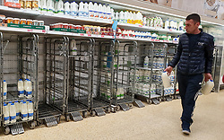 © Licensed to London News Pictures. 21/09/2021. London, UK. A shopper walks past empty shelves of fresh milk, just after 8am this morning in Sainsbury's, north London, Fears of food shortages grow after two of the UK's biggest Carbon Dioxide (CO2) producers halted production last week due to soaring gas prices. UK food producers and supermarkets are warning that shoppers are likely to face food shortage caused by a lack of gas could hit this week. Photo credit: Dinendra Haria/LNP