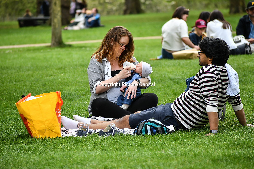 A mother feeds baby with milk bottle at Green park on 23 April 2019, London, UK.