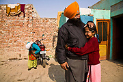 Jasbir Kaur hugs her father as he prepares to leave for work, Chita Kalaan village, Punjab, India