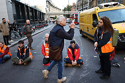 © Licensed to London News Pictures. 25/10/2021. London, UK. Insulate Britain climate change activists block traffic on Bishopsgate in the City of London. The group have restarted their actions to block motorways and major roads causing disruption in the week before the COP26 climate meeting in Glasgow on 31/10/2021. Photo credit: Ben Cawthra/LNP