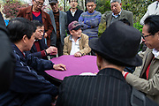 Men play a game of cards on a bench at Fuxing Park in Shanghai, China, on Sunday, April 10, 2016. An rapidly ageing demographic is one of the main challenges facing China as society is greying before the country became a developed nation.