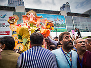07 SEPTEMBER 2014 - BANGKOK, THAILAND: Men carry the large statue of Ganesh to a waiting truck during the Ganesh Festival at Central World in Bangkok. Ganesh Chaturthi, also known as Vinayaka Chaturthi, is a Hindu festival dedicated to Lord Ganesh. It is a 10-day festival marking the birthday of Ganesh, who is widely worshiped for his auspicious beginnings. Ganesh is the patron of arts and sciences, the deity of intellect and wisdom -- identified by his elephant head. The holiday is celebrated for 10 days, in 2014, most Hindu temples will submerge their Ganesh shrines and deities on September 7.     PHOTO BY JACK KURTZ