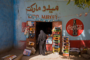 Exterior of a small community shop in a village near Medinet Habu on the West Bank of Luxor, Nile Valley, Egypt. This scene is typical of the quiet pace of rural everyday life, far away from the chaotic capital, Cairo whose government controls the policies that affect the people of small villages.