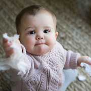 A ten month old baby girl offers a tissue directly towards the camera while playing. Photo Tim Clayton