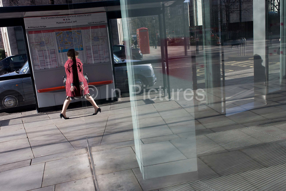A woman seemingly passes through her own reflection in a humerous scene in plate glass of a pedestrian walking through a shopping complex in the financial City of London. The symmetrical reflection doubles the person's presence in the window of an office, on a corner  in what's called the Square Mile after its ancient Roman walled past.