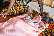 A baby lying next to her mother on the children's ward. St Walburg's Hospital, Nyangao. Lindi Region, Tanzania.