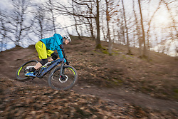 Mountain biker speeding on e-bike through forest track, Bozen, Trentino, Italy