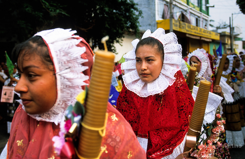"""Juchitàn, Vela Cheguigo. Tehuanas with traditional """"Huipil Grande"""", often worn as hood. The tehuanas are the archetype of an ancient and legendary Mexico, told in the murales of Diego Rivera and impersonated also by Frida Kalho that often wore these traditional dresses. But these showy dresses, and the rich golden ornaments that accompany them, are above all an instrument of auto-representation for these active women which the control of the local markets confers an independent economic power that is reflected in the self confidence. Even in the development of the festivities, where the women often dance a lot among them while the men remain seated watching."""