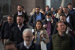 © Licensed to London News Pictures. 11/05/2021. London, UK. Commuters head to work during rush hour at London Bridge in central London. The Prime Minister Boris Johnson has unveiled the latest stage in coronavirus lockdown easing yesterday as 'the single biggest step on our roadmap'. However, advice to work from home where possible will stay in place. Photo credit: Marcin Nowak/LNP