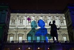 © Licensed to London News Pictures. 17/01/2018. London, UK. A statue of Sir Joshua Reynolds stands over a projection entitled 'Love Motion ?by Rhys Coren' at the Royal Academy  Courtyard during the Lumiere London festival. Running from 18th-21st January 2018 more than 50 artworks? are transforming the capital's streets, buildings and public spaces into an immersive nocturnal art exhibition of light and sound. Locations include King's Cross, Fitzrovia, Mayfair, West End, Trafalgar Square, Westminster, Victoria, South Bank and Waterloo. Photo credit: Peter Macdiarmid/LNP