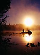 Misty morning sunrise silhouetting Karen Crosby and Scott Stolnack paddling canoe on Loon lake near Soldotna, Kenai Peninsula, Alaska.