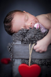 Close-up of cute newborn baby girl sleeping with pacifier on winebox, Fuerstenfeldbruck, Bavaria, Germany