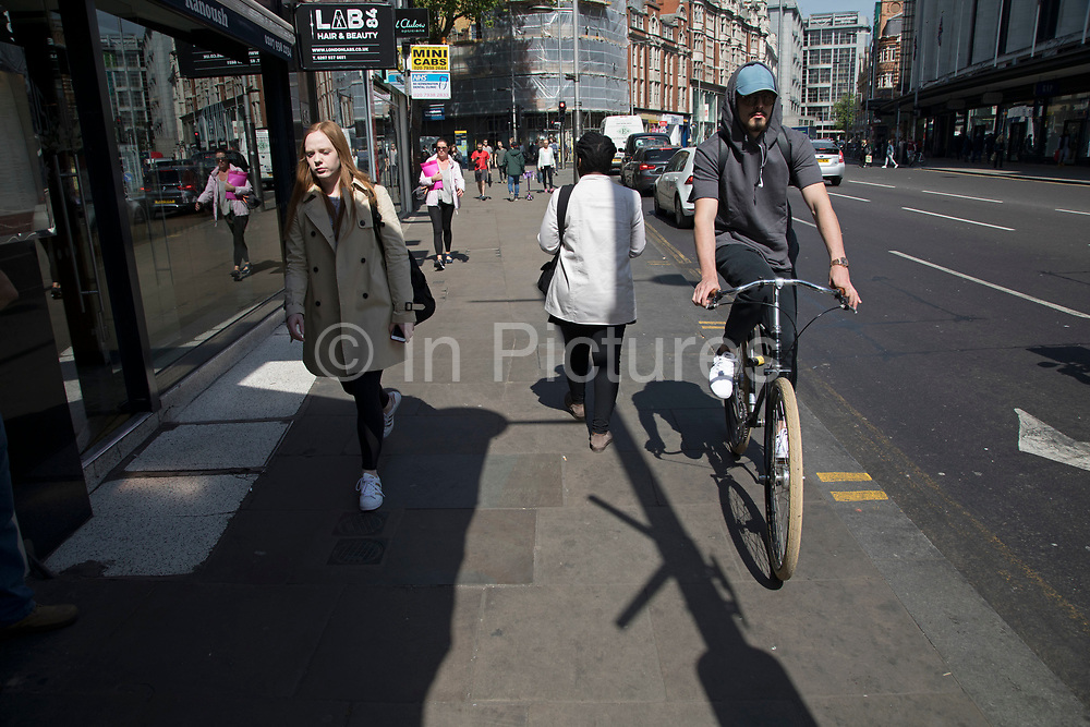Cycling on the pavement in London, England, United Kingdom. Cycling has become a very popular mode of transport in the capital as people try to avoid public transport, saving money, getting fit and saving time.