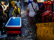 23 NOVEMBER 2017 - YANGON, MYANMAR: A laborer pushes his empty cooler chest to an ice making area in the San Pya Fish Market. San Pya Fish Market is one of the largest fish markets in Yangon. It's a 24 hour market, but busiest early in the morning. Most of the fish in the market is wild caught but aquaculture is expanding in Myanmar and more farmed fresh water fish is being sold now than in the past.    PHOTO BY JACK KURTZ