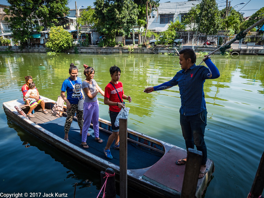 16 FEBRUARY 2017 - THEPHARAK, SAMUT PRAKAN, THAILAND: A boatman takes passengers across Khlong Samrong in his small boat, which he uses as a ferry, in the Bangkok suburbs. The boatman pulls it across using a system of ropes and pulleys. He's been working on the boat since he was a child. Small ferries like this used to be common in Bangkok but many of the khlongs (the canals that used to crisscross Bangkok) have been filled in and bridges have been across the remaining khlongs. Now there are only a handful of the ferries left. This ferry charges 2 Baht (the equivalent of about .06¢ US) per person to take a person across the khlong.      PHOTO BY JACK KURTZ