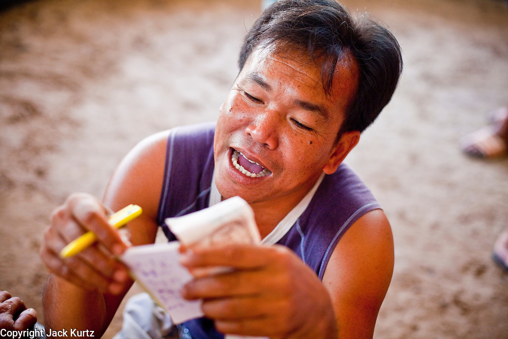 11 APRIL 2010 - PLA PAK, NAKHON PHANOM, THAILAND: A bookie tallies his take after a long shot bird he put a bet on won in a cockfight in northeastern Thailand. Cockfighting is enormously popular in rural Thailand. A big fight can bring the ring operator as much as 200,000 Thai Baht (about $6,000 US), a large sum of money in rural Thailand. Fighting cocks live for about 10 years and only fight for 2nd and 3rd years of their lives. Most have only four fights per year. Fighting cocks in Thailand do not wear the spurs or razor blades that they do in some countries and most times the winner is based on which rooster stops fighting or tires first rather than which is the most severely injured. Although gambling is illegal in Thailand, many times fight promoters are able to get an exemption to the gambling laws and a lot of money is wagered on the fights. Many small rural communities have at least one cockfighting arena.   PHOTO BY JACK KURTZ