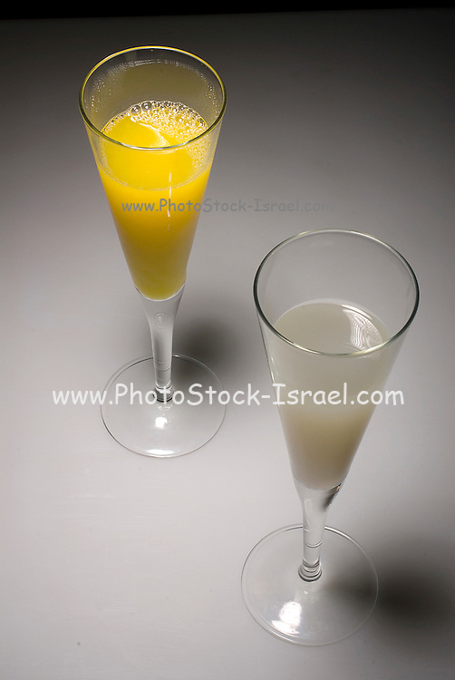 An elegant glass of grapefruit juice and a glass of orange juice on a black and white background