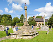 People walking to church past medieval preaching cross, Great Bedwyn churchyard, Wiltshire, England, UK