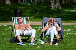 © Licensed to London News Pictures. 27/05/2021. LONDON, UK.  A couple on deckchairs enjoying the sunshine and warmer temperatures in St James's Park after an unusually wet May so far.  The forecast for the Bank Holiday weekend is fine weather.  Photo credit: Stephen Chung/LNP