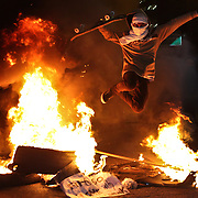 A protester affiliated with the Black Bloc anarchist group jumps over a fire, lit on a major road, during a protest aimed at lowering metro fares in Sao Paulo on Thursday, June 19, 2014. Credit: Byron Smith