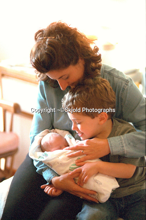 Aunt and cousin visiting baby boy after delivery ages 35 and 5 .  Edina Minnesota USA