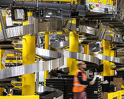 "© Licensed to London News Pictures . 04/12/2019. Manchester , UK . Spiral conveyor belts carry containers of stock from a lower level of the warehouse up to the level above . Inside the ""MAN1"" Amazon fulfilment centre warehouse at Manchester Airport in the North West of England . Photo credit : Joel Goodman/LNP"