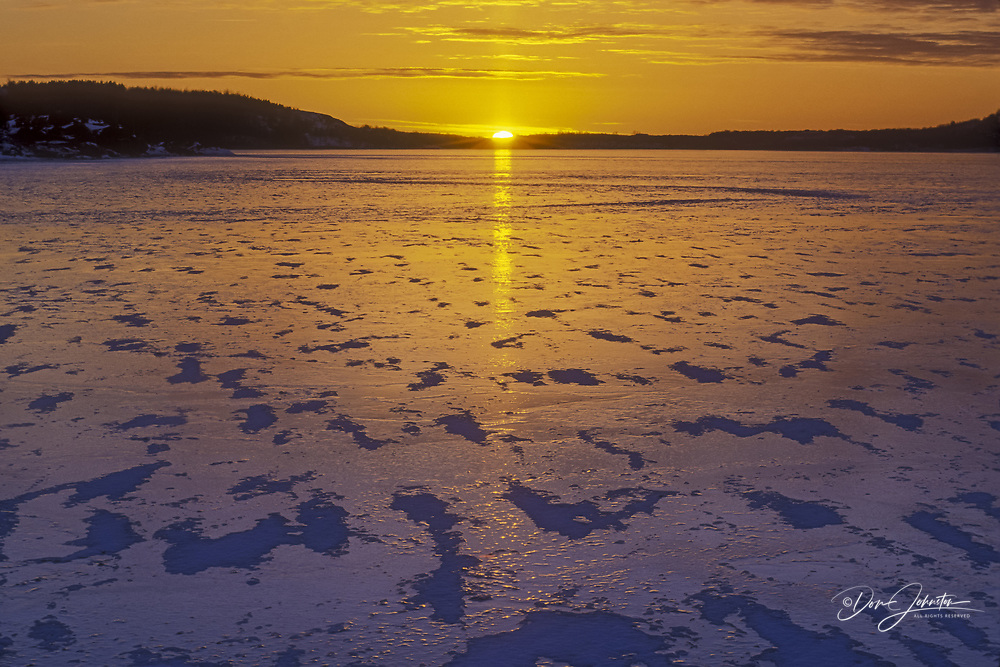 Setting sun reflections in fresh ice on Kelly Lake in early winter, Sudbury, Ontario, Canada