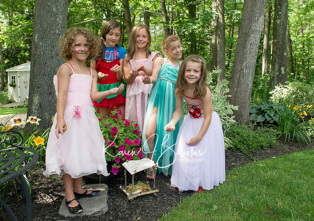 """""""Fairies"""" from the Boys and Girls Club add sparkle to their fairy houses placed among the gardens at Robert King and Elaine Muller's home prior to Opechee Garden Club's Tour on Saturday.  (Karen Bobotas/for the Laconia Daily Sun)"""