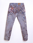 Jeans with a lot of paint splatters back view.