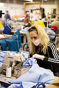 """Mcc0094887. Daily Telegraph <br /> <br /> DT News<br /> <br /> Workers at a fashion manufacturing site in north London making scrubs for the NHS as supplies have dried up from the far east . <br /> <br /> Fashion Enter Ltd based in Haringay have a contract for 10,000 sets of scrubs and 12,000 pairs of trousers, the fabric arrived late wednesday afternoon . <br /> <br /> Fashion Enter CEO Jenny Holloway, a former retail buyer who also runs a Fashion Technology Academy teaching stitching and pattern skills . She hopes to continue supporting the NHS and says manufacturing is """" categorically not too expensive in UK """".<br /> with improved speed of response and ethical manufacturing practices .<br /> <br /> London 3 April 2020"""