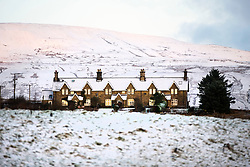 © Licensed to London News Pictures. 25/11/2017. Gearstones UK. A row of snow covered house in Gearstones this morning in the shadow of Whernside mountain after a night of snow fall in the Yorkshire Dales. Photo credit: Andrew McCaren/LNP