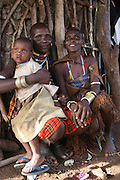 Africa, Tanzania, members of the Datoga tribe Woman young daughter and baby in traditional dress, beads and earrings. Beauty scarring can be seen around the eyes, April 2006