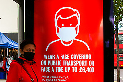 © Licensed to London News Pictures. 16/10/2020. London, UK. A woman wearing a face covering at a bus stop, with  the Transport for London's COVID-19 advert informing that face coverings must be worn on public transport, as London moves to COVID-19 tier two restrictions from tonight, following the government's announcement of tougher measures in the capital to manage increasing cases. From midnight tonight, households in London will not be allowed to mix indoors, including in pubs and restaurants.  Photo credit: Dinendra Haria/LNP