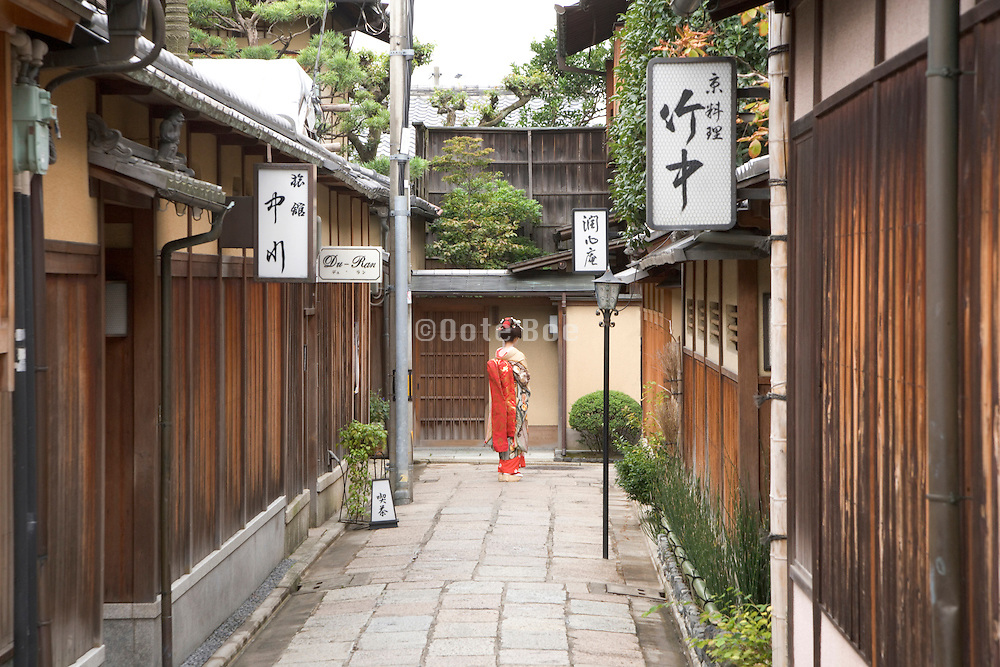 traditionally dressed maiko walking the small streets of Kiyomizu district in Kyoto Japan