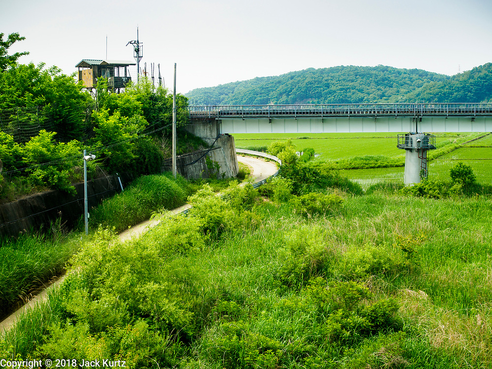 """09 JUNE 2018 - IMJINGAK, PAJU, SOUTH KOREA: A South Korean lookout at the foot of the  """"Freedom Bridge"""" from the South Korean side of the Korean DMZ in Imjingak. The bridge, now closed, is called the Freedom Bridge because it is the bridge POWs returning to the South crossed when they were releases by North Korea after the cease fire was signed. The Bridge could be reopened for train traffic if a peace treaty is signed with North Korea. Imjingak is a park and greenspace in South Korea that is farthest north most people can go without military authorization. The park is on the south bank of Imjin River, which separates South Korea from North Korea and is close the industrial park in Kaesong, North Korea that South and North Korea have jointly operated.     PHOTO BY JACK KURTZ"""