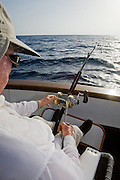 Over the shoulder view of angler in fighting chair with bucket harness and bent fishing pole.